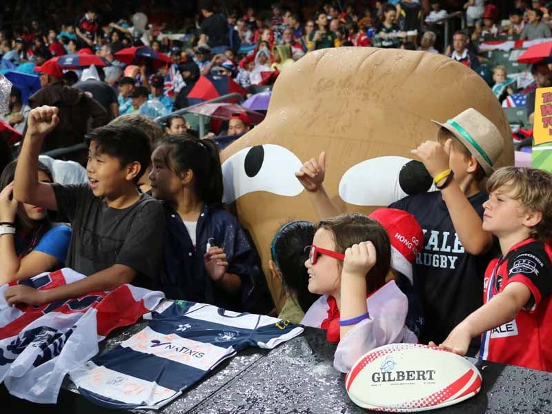 Big Waster returns to HK Sevens to promote waste reduction: Big waster with a crowd of children watching rugby 7