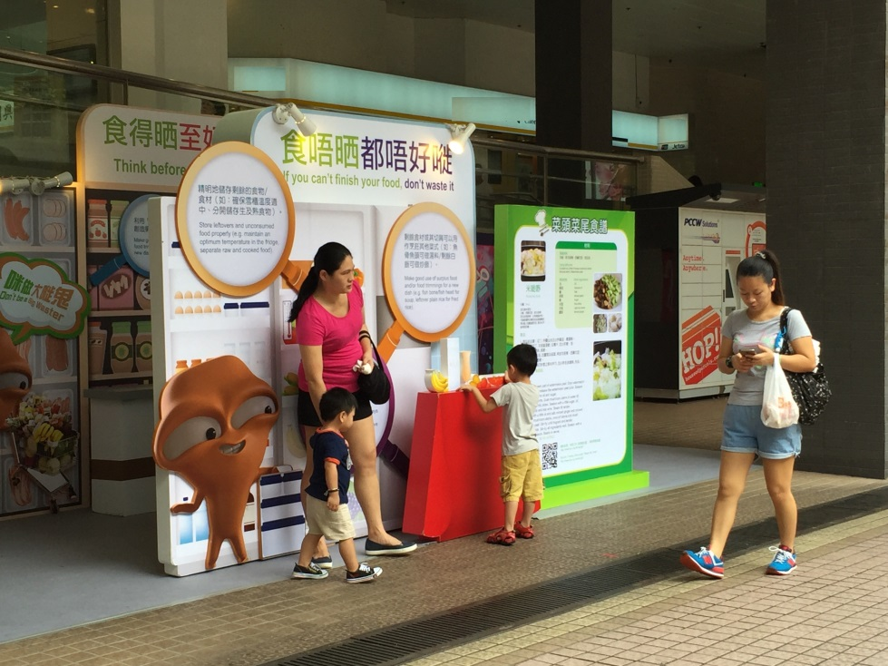Food Wise Hong Kong Campaign to promote food waste reduction at Tuen Mun District :Family looking at the food wise information in the exhibition.
